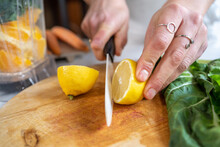 Crop Anonymous Female Cutting Ripe Juicy Lemon With Knife Between Chard Leaves And Blender Bowl In Kitchen