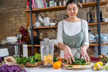 Female Putting Fresh Chard Leaves Blender Bowl With Orange Slices In House Kitchen