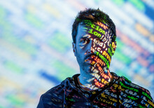 Adult Bearded Male In Hoodie With Multicolored Words On Half Of Face From Projector Light Looking At Camera