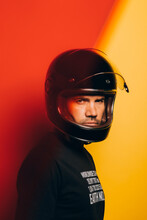 Side View Of Confident Brutal Adult Man In Black Motorcycle Helmet Looking At Camera While Standing Against Colorful Red And Yellow Background