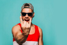 Rebel Young Ethnic Hipster Man In Cap And Black Sunglasses Shouting Expressively And Showing Sign Of Horns While Standing Against Blue Background