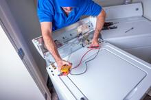 Appliance Repairman In Uniform Fixing A Washing Machine