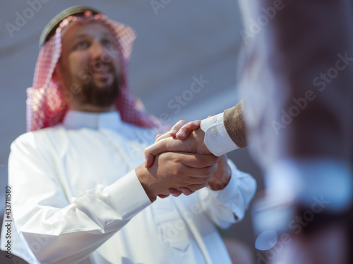 Canvas Print Business meeting with arab man and shaking each other hands in greetings and int
