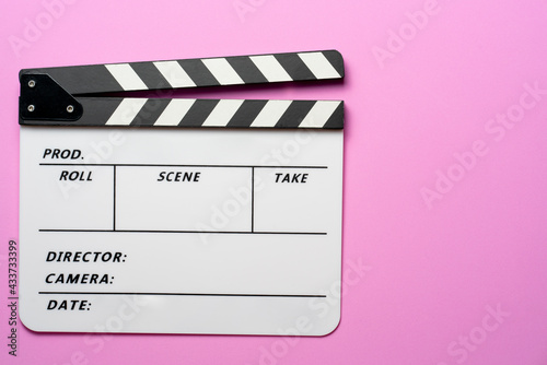 Fototapeta movie clapper on pink table background; film, cinema and video photography concept obraz