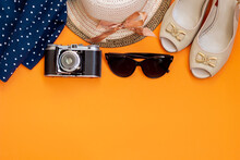 Female Straw Hat With Ribbon,black Sunglasses, Blue Polka Dot Skirt,old Vintage Retro Camera, Sandals Isolated On A Bright Color Orange Background. Top View. Summer Vacation Travel Concept. Copy Space
