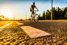 Sunset In The Country, The Cyclist Rides On The Highway. Wide Angle View Of The Level Of The Dividing Line