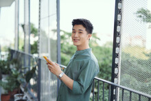 Young Man With Mobile Phone At Home On The Terrace