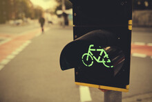 Traffic Light At Cycling Lane Shows Green While Pedestrian Crosses Street In Bakcground - Decorative Toned Light Mood With Selective Focus - Urban Cycling And Traffic Concept
