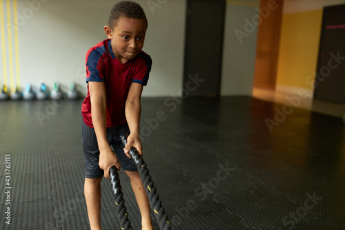 Focused black little boy in sports clothing exercising in gym doing dynamic full body workout using battling ropes waving them up and down. Fitness, determination, endurance and motivation concept - fototapety na wymiar