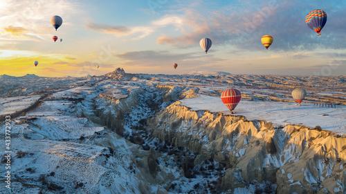 Fotografiet Hot air balloons fly over Cappadocia in winter, Goreme, Turkey.