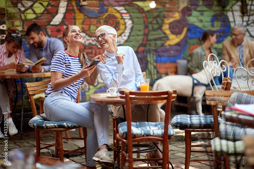 An older woman and her young female friend laughing about a smartphone content they watching while have a drink in the bar. Leisure, bar, friendship, outdoor - fototapety na wymiar