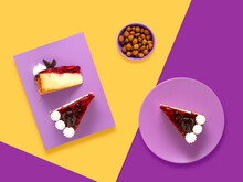 Creative Concept Health Diet Sweet Food Photo Of Painted Plates Dishes Tableware With Nuts Pastry Candy Strawberry Chocolate And Cake On Purple Yellow  Background.
