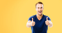 Portrait Of Happy Smiling Man In Blue Casual Clothing, Showing Thumb Up Gesture, Isolated Over Orange Yellow Color Background. Male Model At Studio. Copyspace Area For Ad Sign Text.