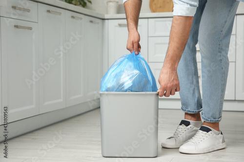 Fototapeta Man taking garbage bag out of bin at home, closeup