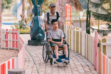 Disabled Child Sitting On Wheelchair And Father Have Fun With Activity On The Outdoor Park On Travel, Lifestyle In Education Age Of Disabled Children, Happy Disability Kid Concept.