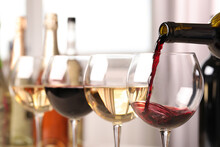 Pouring Red Wine From Bottle Into Glass, Closeup