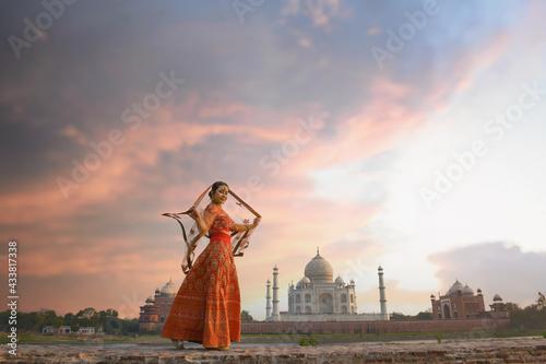 Fototapeta Woman in red saree/sari in the Taj Mahal, Agra, Uttar Pradesh, India