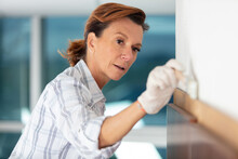 Mature Woman Painting A Wall