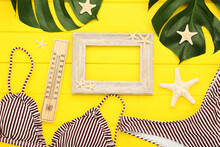 Fashion Swimsuit With Monstera Leafs, Thermometer, Starfishes And Photo Frame On Yellow Wooden Table