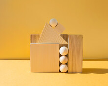 Geometric Composition Of Many Wooden Figures On Yellow Background. Creative And Education Concept.