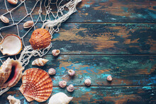Various Sea Shells And Fishing Net On Blue Wooden Background