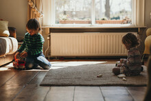 Netherlandian Kids On The Floor Playing Separately With Their Own Toys In A Playroom