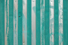 Fragment Of A Wall Made Of Silver-colored Metal Profiled Sheet. The Vertical Stripes Are Partially Green. Background. Texture.
