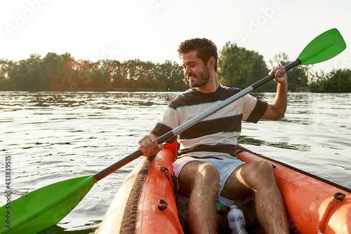 Canvas Print Excited young man smiling while kayaking in a lake, surrounded by peaceful natur