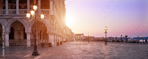 Banner, San Marco square at sunrise early in the morning. Venice or Venezia city, Italy, Europe. Panoramic composition, illuminated architecture, image toned orange. Sunrise, sun flare.