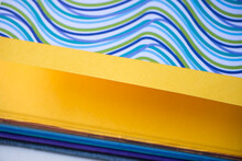 Colourful Blank Book With Pages Open Flat To Yoke Yellow Paper And Wavy Pattern In Blue