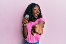 Beautiful African Young Woman Singing Song Using Microphone Pointing To Camera Celebrating Crazy And Amazed For Success With Open Eyes Screaming Excited.
