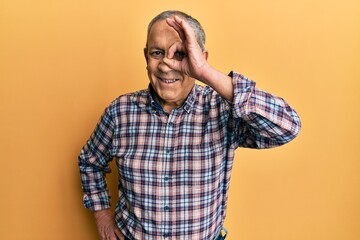 Handsome senior man with grey hair wearing casual shirt doing ok gesture with hand smiling, eye looking through fingers with happy face.