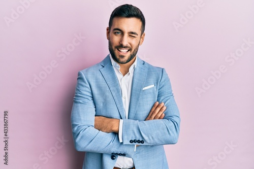 Wallpaper Mural Young hispanic businessman wearing suit with arms crossed gesture winking looking at the camera with sexy expression, cheerful and happy face
