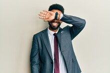 Handsome Hispanic Man With Beard Wearing Business Suit And Tie Covering Eyes With Arm Smiling Cheerful And Funny. Blind Concept.