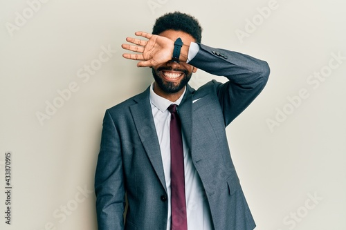 Photo Handsome hispanic man with beard wearing business suit and tie covering eyes with arm smiling cheerful and funny