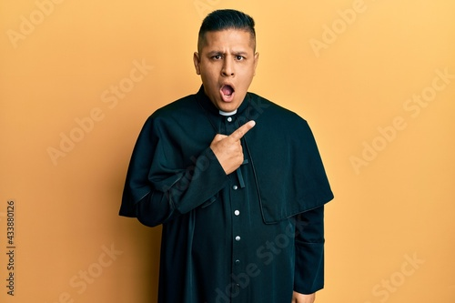 Stampa su Tela Young latin priest man standing over yellow background surprised pointing with finger to the side, open mouth amazed expression
