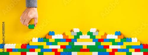 Foto hand building up a wall by stacking up plastic block