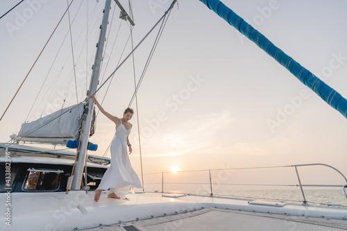 Fototapeta Woman wearing white dress relax on sailing yacht, romantic sunset