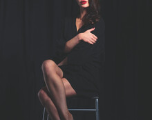 Beautiful Woman Sitting A Chair, Isolated On Lack Background. Beautiful Woman.