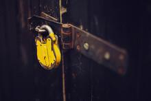 Yellow Padlock On A Wooden Door. Symbol Of Security.