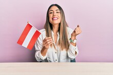 Young Hispanic Woman Holding Austria Flag Sitting On The Table Screaming Proud, Celebrating Victory And Success Very Excited With Raised Arm