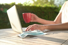 Woman Using Her Computer Laptop With Cup Of Coffee And Face Mask On Table In Her Garden. Work At Home While Quarantine Or Lockdown During Epidemic.