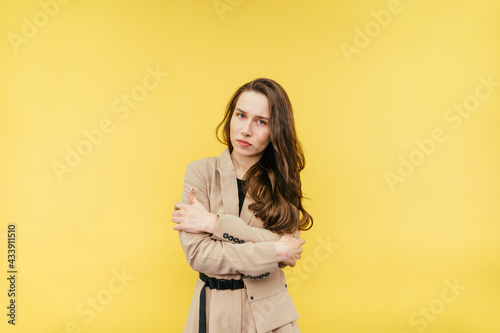 Obraz na płótnie Frozen woman in a suit isolated on a yellow background, hugged herself and looked at the camera with a sad face