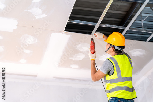 Obraz na płótnie Construction workers using an electric drill are install the ceiling house in the building under construction, Ceiling installation ideas