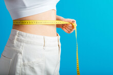 Slim Woman Measures Her Waist Waistline With Measuring Tape. Healthy Body Shaping Weight Loss Concept. Slim Waist Small Belly In Big White Denim Pants Isolated Over Blue Color Background. Copy Space