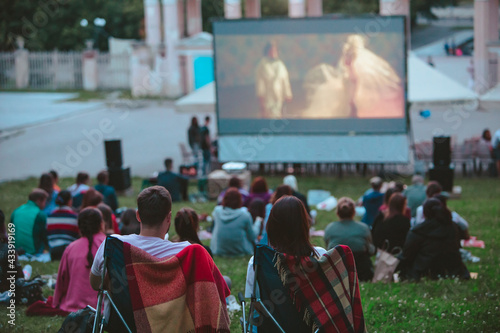 Photo couple sitting in camp chairs in front of movie screen at open air cinema