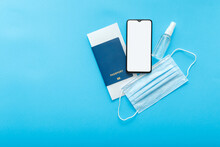 Mockup Smartphone Blank Screen Passport Plane Tickets Medical Mask And Sanitizer. Mockup For Green Pass Covid Test App. Concept Travel Vaccination Flat Lay On Color Blue Background With Copy Space