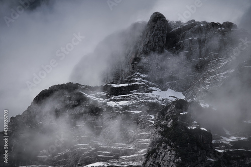 Fotografía Dark mood -  dramatic clouds and fogs over the mountains and parts with snow