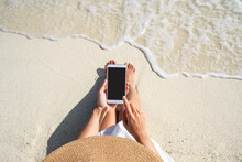 Young Woman Using Mobile Phone At Beautiful Tropical White Sand Beach With Wave Foam And Transparent Sea, Summer Vacation And Travel Concept With Copy Space