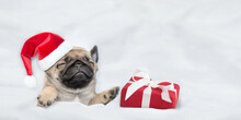 Pug Puppy Wearing Red Santa Hat Sleeps With Gift Box Under White Blanket At Home. Top Down View. Empty Space For Text